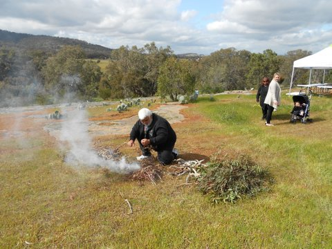 Smoking Ceremony - Ron from the Dja Dja Wurrung lights the fire, Bec and Brenda look on